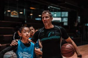 Ganon Baker with arm around Chinese basketball player. He is sharing basketball knowledge with the player.