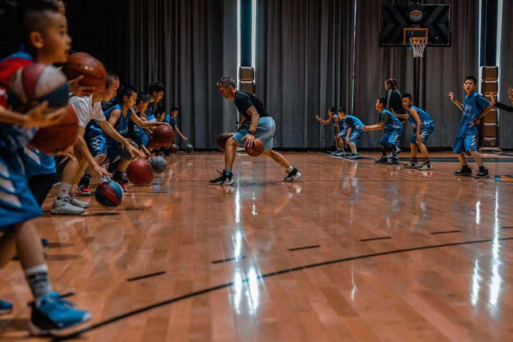 Ganon Baker demonstrating a dribble move to a gym full of kids. They are beginning to work on this ball handling move.
